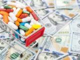 Shopping cart filled with pills on a background of money