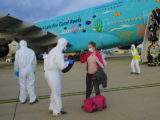 FILE - In this Feb. 2, 2020 file photo, a worker wearing a protective suit checks the luggage o ...